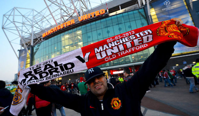 A Real Madrid supporter poses holding a scarf ahead of the UEFA Champions League round of 16 second leg football match between Manchester United and Real Madrid at Old Trafford in Manchester, north west England, on March 5, 2013. AFP PHOTO / PAUL ELLIS (Photo credit should read PAUL ELLIS/AFP/Getty Images)