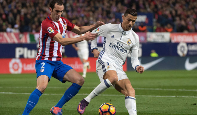 TOPSHOT - Atletico Madrid's Uruguayan defender Diego Godin (L) vies with Real Madrid's Portuguese forward Cristiano Ronaldo during the Spanish league football match Club Atletico de Madrid vs Real Madrid CF at the Vicente Calderon stadium in Madrid, on November 19, 2016. / AFP / CURTO DE LA TORRE (Photo credit should read CURTO DE LA TORRE/AFP/Getty Images)