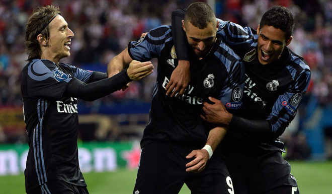 Real Madrid's French forward Karim Benzema (C), Real Madrid's Croatian midfielder Luka Modric (L) and Real Madrid's French defender Raphael Varane celebrate a goal during the UEFA Champions League semifinal second leg football match Club Atletico de Madrid vs Real Madrid CF at the Vicente Calderon stadium in Madrid, on May 10, 2017. / AFP PHOTO / GERARD JULIEN (Photo credit should read GERARD JULIEN/AFP/Getty Images)