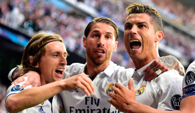 Real Madrid's Portuguese forward Cristiano Ronaldo (R) celebrates with Real Madrid's Croatian midfielder Luka Modric (L) and Real Madrid's defender Sergio Ramos after scoring during the UEFA Champions League semifinal first leg football match Real Madrid CF vs Club Atletico de Madrid at the Santiago Bernabeu stadium in Madrid, on May 2, 2017. / AFP PHOTO / GERARD JULIEN (Photo credit should read GERARD JULIEN/AFP/Getty Images)