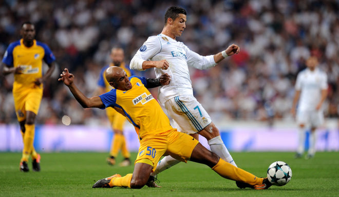 MADRID, SPAIN - SEPTEMBER 13: Carlao of Apoel FC tackles Cristiano Ronaldo of Real Madrid during the UEFA Champions League group H match between Real Madrid and APOEL Nikosia at Estadio Santiago Bernabeu on September 13, 2017 in Madrid, Spain. (Photo by Denis Doyle/Getty Images)