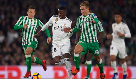 SEVILLE, SPAIN - JANUARY 13: Vinicius Jr from Real Madrid CF (C) followed by Andres Guardado by Real Betis Balompie (L) and Giovani Lo Celso from Real Betis Balompie (R) during La Liga match between Real Betis Balompie and Real Madrid at Estadio Benito Villamarin on January 13, 2019 in Seville, Spain. (Photo by Aitor Alcalde / Getty Images)